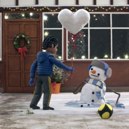 The boy gives a snowman a heart shaped snow balloon